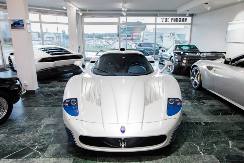 A white-and-blue Maserati MC12 for sale at an exotic car dealership in Switzerland