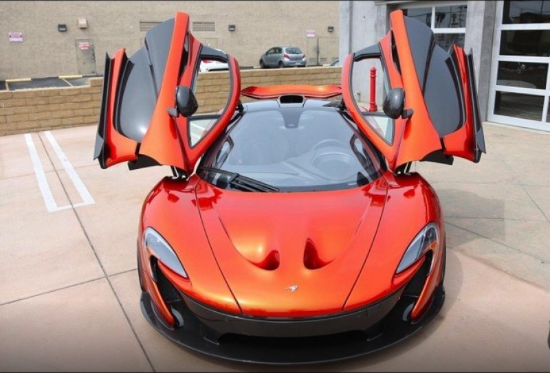 An orange McLaren P1 for sale at a luxury automobile dealer in Los Angeles
